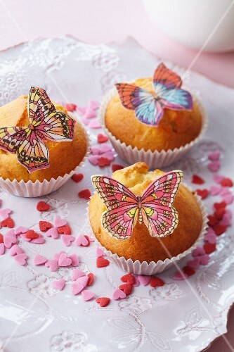 Muffins decorated with butterflies made from edible paper and sugar hearts