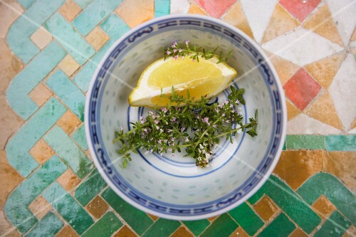 Thyme and a lemon wedge in a bowl