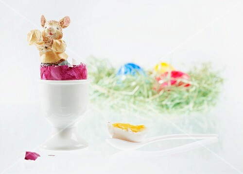 An Easter bunny figurine in a boiled egg with the top cut off, with an Easter nest of colourful eggs in the background
