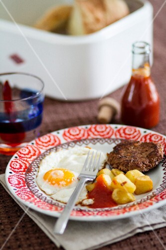 A fried egg, fried potatoes and Frikadelle (German burger), served with home-made ketchup