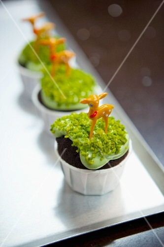 Chocolate cupcake topped with pistachios and a deer figurine