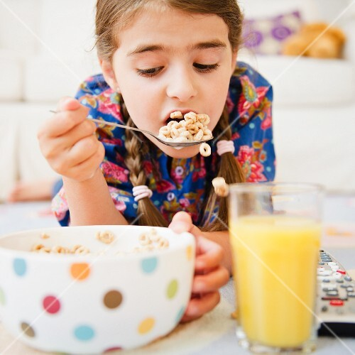 Girl ( 6-7) eating cereals