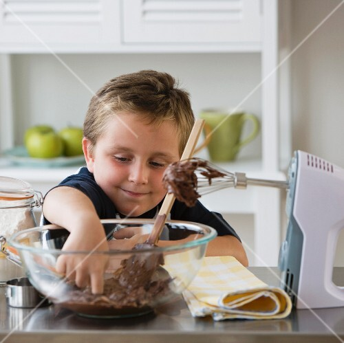Boy sticking finger into bowl of batter