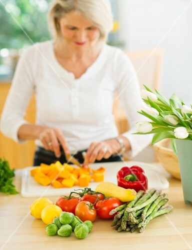 Portrait of senior woman cutting vegetables in kitchen