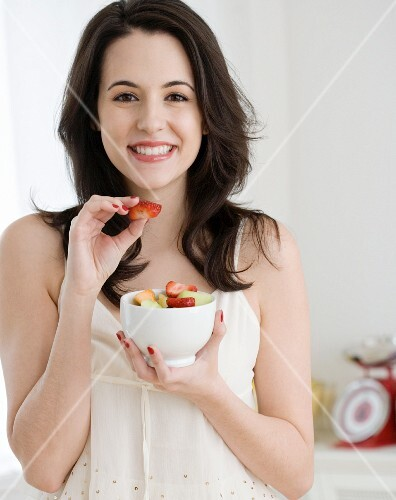 Portrait of woman eating fruit salad