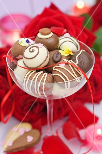 Assorted chocolate candies in a champagne glass, red roses