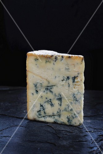 A wedge of Stilton on a slate board