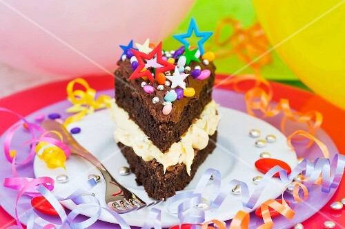 A piece of chocolate cake with colorful sprinkles and candy decorations for a party
