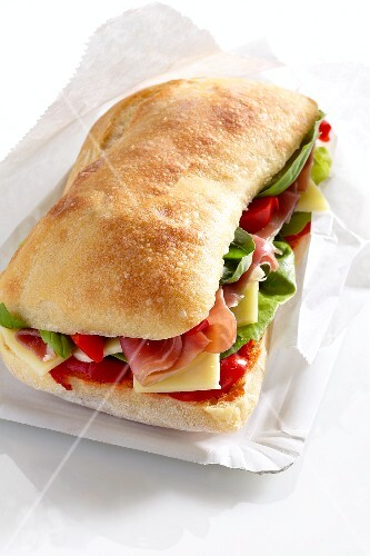 A sandwich filled with dry-cured ham, salad and cheese