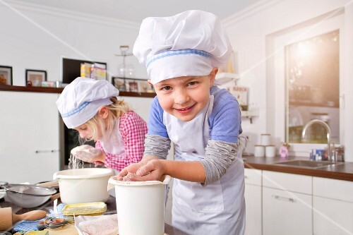 Germany, Girl and boy making dough in kitchen