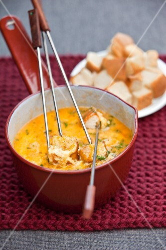 Cheese fondue with herbs and bread cubes