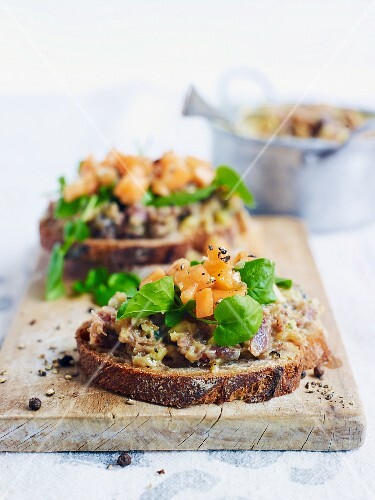 Slices of bread topped with duck rillettes, melon and watercress