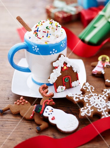 A Mug of Hot Chocolate with Whipped Cream and Sprinkles with Decorated Christmas Cookies