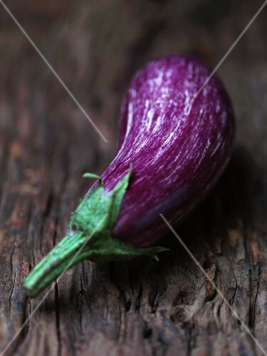 An aubergine on a wooden surface