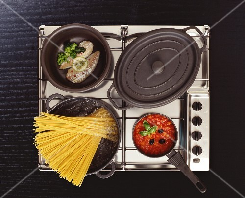 Stainless steel hob with boiling pasta water, fish in a pan, tomato sauce and stew pot