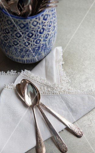 Cutlery holder with a blue and white design; to one side, a lace-edged napkin and three antique silver spoons