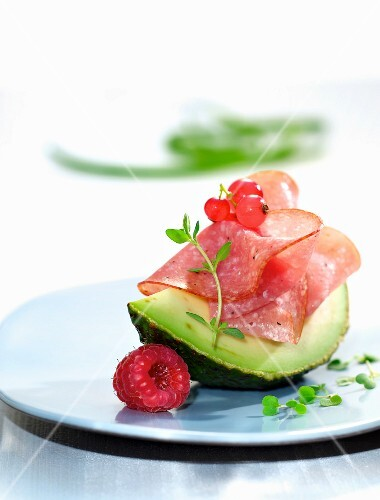 A wedge of avocado with salami and berries