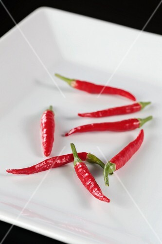 Several fresh red chillies on a plate