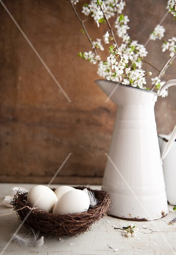 Eggs in a nest and an enamel jug with sprays of flowers