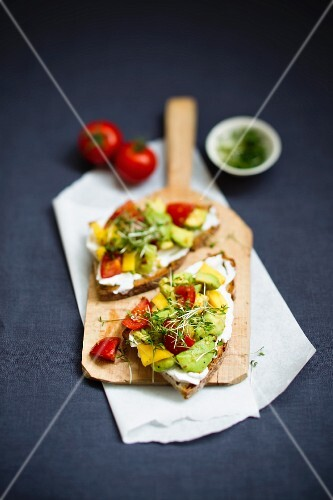 Rustic bread topped with avocado, mango, cherry tomatoes and cress