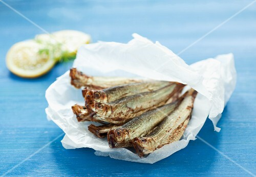 A pile of sprats on crumpled white paper on a blue surface