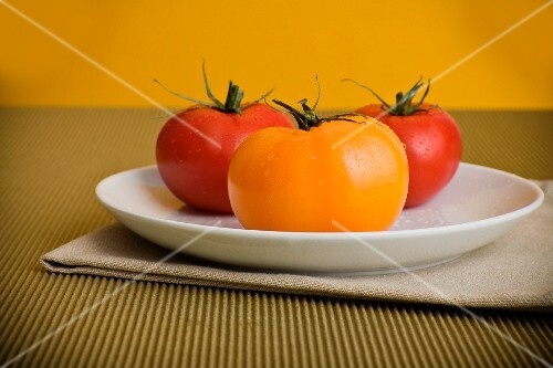 Yellow and Red Tomatoes on a White Plate