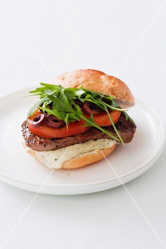 A burger with rump steak, tomatoes, olives and rocket (Italy)