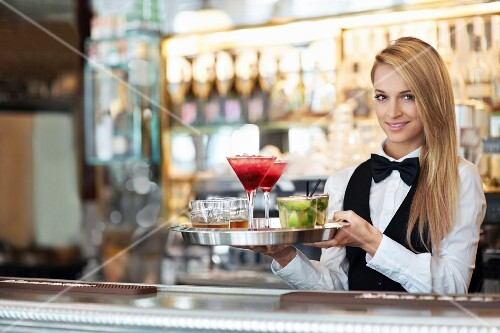A waitress holding a tray of cocktails in a restaurant