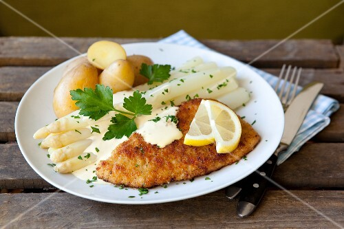 White asparagus and a schnitzel with Hollandaise sauce and potatoes