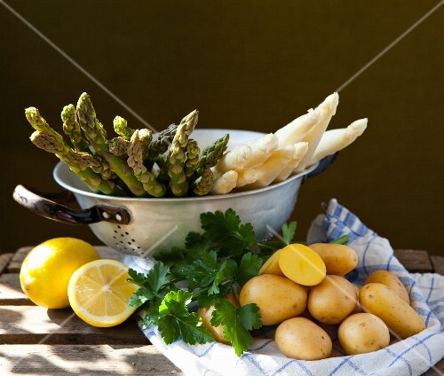 Asparagus in a sieve with lemons, parsley and potatoes