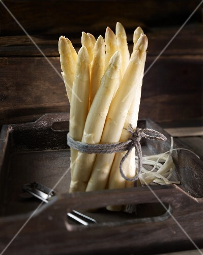 A bunch of white asparagus on a wooden tray