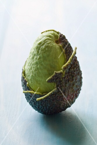 An avocado, partly peeled