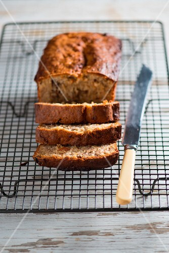 Banana and walnut bread, partly sliced, on a cooling rack