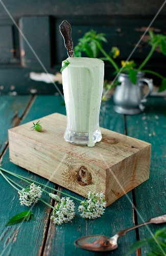 Mint Yogurt Sauce in a Tall Glass with a Spoon on a Block of Wood