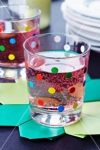 A drinking glass decorated with colourful dots