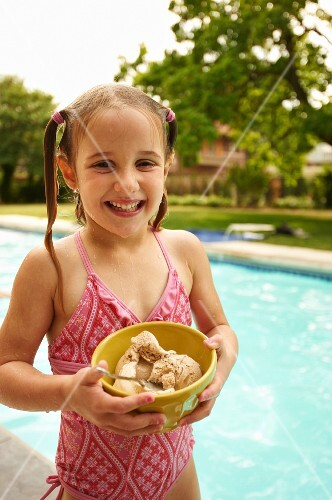 Young Girl Holding a Bowl of Ice Cream Next to a Pool