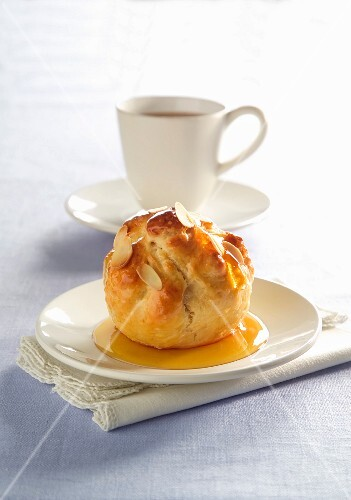 An apple in pastry in front of a cup of coffee