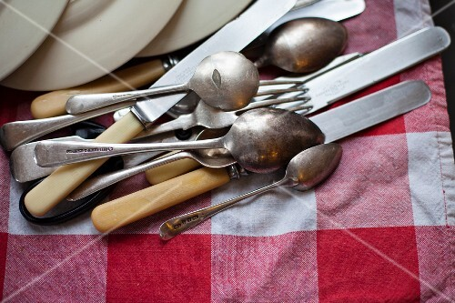 Cutlery and plates lying on a tea towel after being washed up