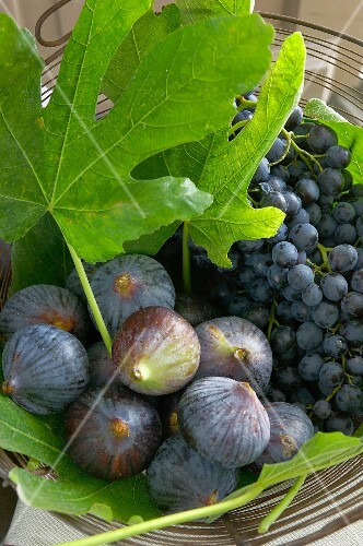 Fresh figs with leaves and black grapes in a wire basket