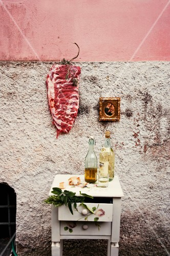 Raw pork ribs hanging on the wall of a house, next to a a gold-framed picture
