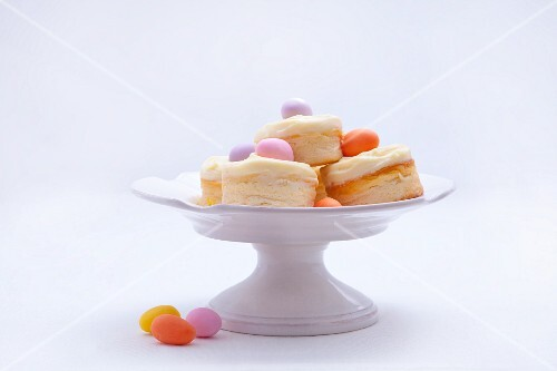 Mini cheesecakes with vanilla custard and marzipan eggs on a cake stand