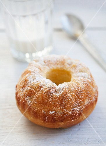 A mini Bundt cake with pieces of pear and icing sugar
