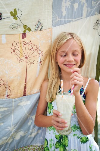 A Young Girl Holding a Milkshake with Two Straws