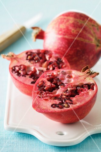 A whole and a halved pomegranate on a chopping board with a knife