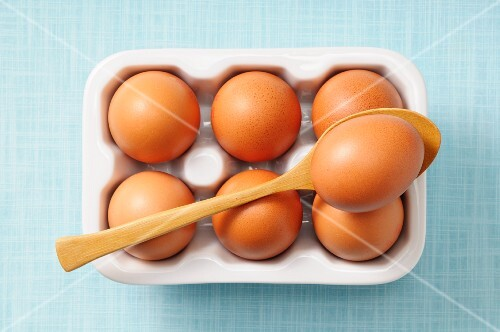 Brown eggs in a box and on a spoon (view from above)