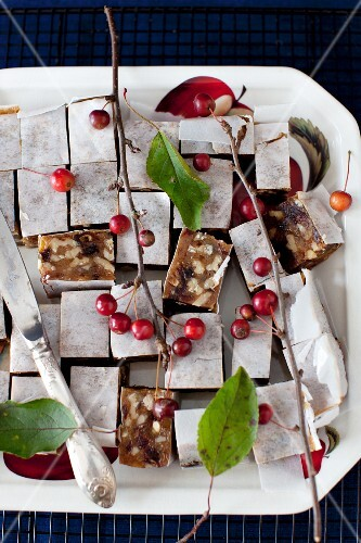 Panforte Squares on a Platter with Berries and a Knife