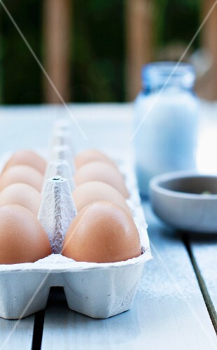 Fresh Eggs in a Carton on an Outdoor Table