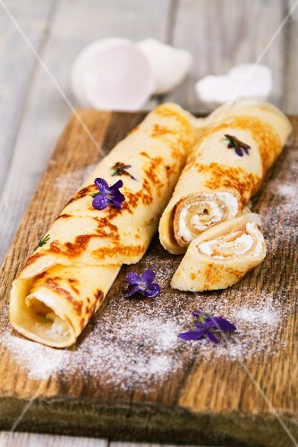 Pancakes filled with cream cheese, with violets