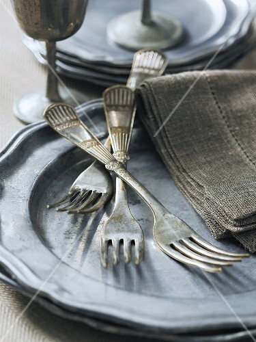 Old silver forks on a pewter plate