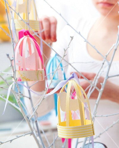 Woman decorating white twigs with paper bird cages